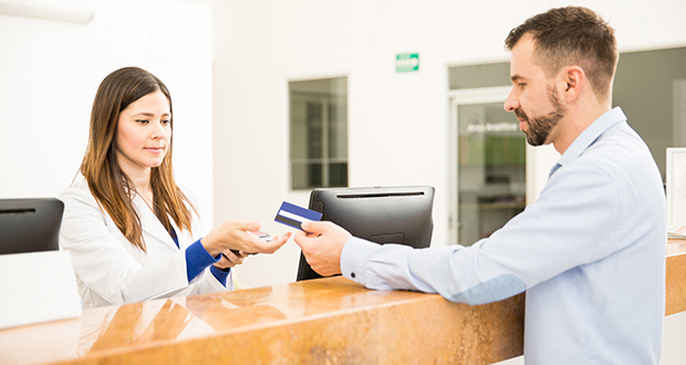 Receptionist taking payment with credit card